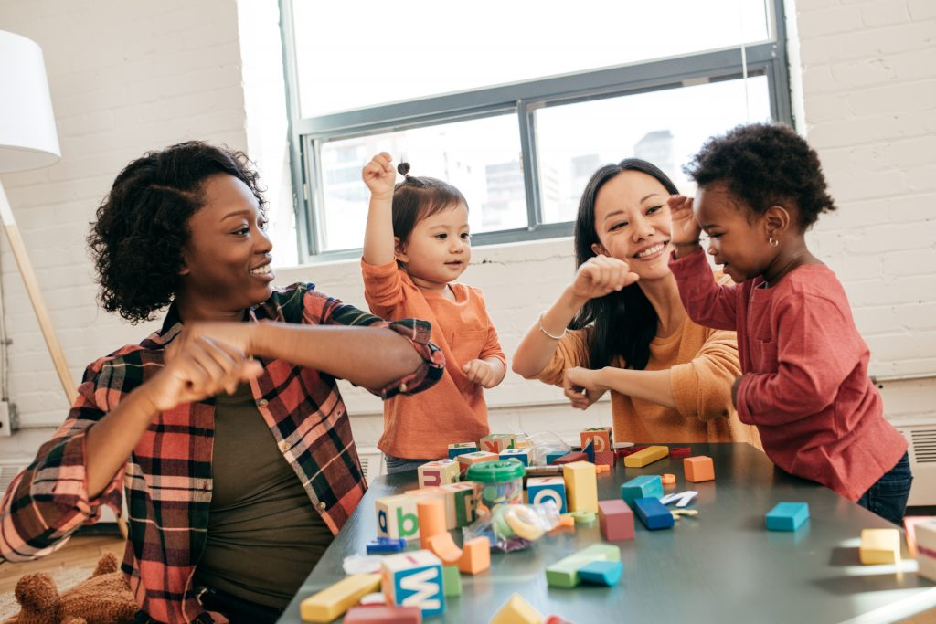 Two mom and daughter pairs, each pair of a different race and skin tone, sit on the floor and dance in front of a table of blocks.